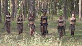 Mujeres jovenes en trajes de teatro de los habitantes o de los diablos del bosque que bailan danza árabe en funcionamiento de la  almacen de video