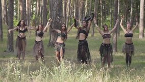 Mujeres jovenes en trajes de teatro de los habitantes o de los diablos del bosque que bailan en funcionamiento de la demostración almacen de metraje de vídeo