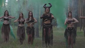 Mujeres jovenes en trajes de teatro de los habitantes o de los diablos del bosque que bailan en funcionamiento de la demostración metrajes