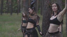 Mujeres jovenes en trajes de teatro de los habitantes o de los diablos del bosque que muestran funcionamiento en bosque encantado almacen de metraje de vídeo