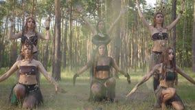 Mujeres jovenes en trajes de teatro de los habitantes o de los diablos del bosque que muestran funcionamiento en bosque encantado metrajes