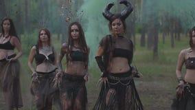 Mujeres jovenes en trajes de teatro de los habitantes o de los diablos del bosque que muestran funcionamiento en bosque encantado almacen de video