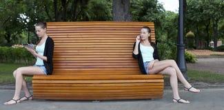 Mujeres jovenes en un banco de parque del verano Imagen de archivo libre de regalías