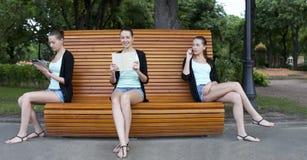 Mujeres jovenes en un banco de parque del verano Fotos de archivo libres de regalías