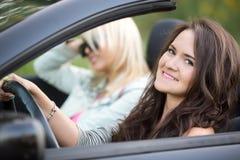 Mujeres jovenes en un viaje del coche Imagenes de archivo