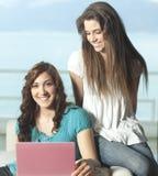 Mujeres jovenes felices con el netbook Foto de archivo