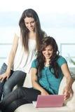 Mujeres jovenes felices con el netbook Foto de archivo libre de regalías