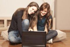 Mujeres jovenes felices con la computadora portátil en el suelo Foto de archivo libre de regalías