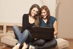 Mujeres jovenes felices con la computadora portátil en el suelo Fotos de archivo libres de regalías