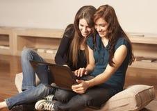 Mujeres jovenes felices con la computadora portátil en el suelo Imágenes de archivo libres de regalías