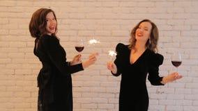 Mujeres jovenes felices con las bengalas y copas de vino en partido metrajes