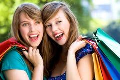Mujeres jovenes felices con los bolsos de compras Imágenes de archivo libres de regalías