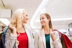 Mujeres jovenes felices con los panieres en alameda Imagen de archivo libre de regalías