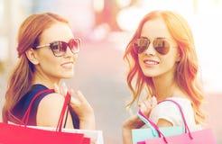 Mujeres jovenes felices con los panieres en ciudad Imagen de archivo libre de regalías
