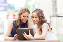 Mujeres jovenes felices con PC de la tableta en el café al aire libre Foto de archivo libre de regalías