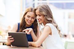 Mujeres jovenes felices con PC de la tableta en el café al aire libre Imagen de archivo libre de regalías
