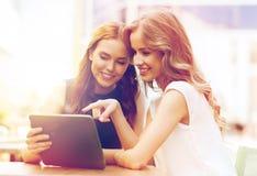 Mujeres jovenes felices con PC de la tableta en el café al aire libre Imagenes de archivo