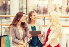 Mujeres jovenes felices con PC y los panieres de la tableta Foto de archivo libre de regalías