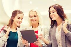 Mujeres jovenes felices con PC y los panieres de la tableta Fotografía de archivo