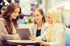Mujeres jovenes felices con PC y los panieres de la tableta Fotos de archivo