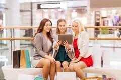 Mujeres jovenes felices con PC y los panieres de la tableta Imágenes de archivo libres de regalías