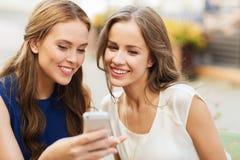 Mujeres jovenes felices con smartphone en el café al aire libre Foto de archivo libre de regalías
