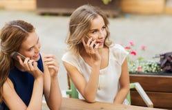 Mujeres jovenes felices con smartphones en el café al aire libre Imágenes de archivo libres de regalías