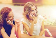 Mujeres jovenes felices con smartphones en el café al aire libre Imagen de archivo libre de regalías