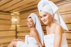 mujeres jovenes felices cubiertas con las toallas relxing en sauna y la mirada fotografía de archivo libre de regalías
