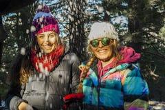 Mujeres jovenes felices debajo de los copos de nieve en la montaña Fotografía de archivo libre de regalías