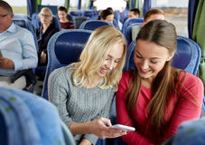 Mujeres jovenes felices en autobús del viaje con smartphone Fotos de archivo