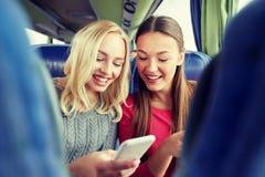 Mujeres jovenes felices en autobús del viaje con smartphone Foto de archivo libre de regalías