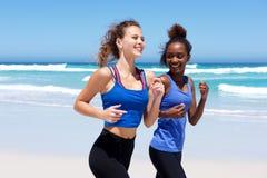 Mujeres jovenes felices que activan en la playa Fotos de archivo libres de regalías