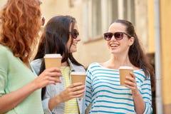 Mujeres jovenes felices que beben el café en la calle de la ciudad Imagen de archivo libre de regalías