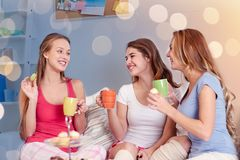 Mujeres jovenes felices que beben té con los dulces en casa Imagen de archivo libre de regalías