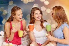 Mujeres jovenes felices que beben té con los dulces en casa Fotos de archivo libres de regalías