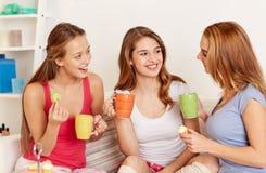 Mujeres jovenes felices que beben té con los dulces en casa Imagenes de archivo