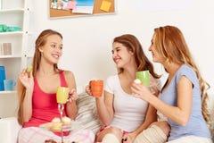 Mujeres jovenes felices que beben té con los dulces en casa Foto de archivo