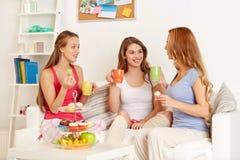 Mujeres jovenes felices que beben té con los dulces en casa Fotos de archivo
