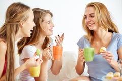 Mujeres jovenes felices que beben té con los dulces en casa Fotografía de archivo