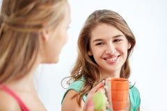 Mujeres jovenes felices que beben té con los dulces en casa Imágenes de archivo libres de regalías