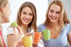 Mujeres jovenes felices que beben té con los dulces en casa Imagen de archivo