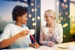 Mujeres jovenes felices que beben té o el café en el café Imágenes de archivo libres de regalías
