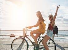 Mujeres jovenes felices que disfrutan de paseo de la bici fotos de archivo
