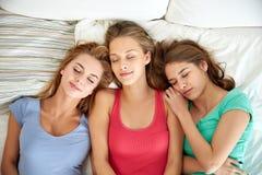 Mujeres jovenes felices que duermen en cama en casa Imagen de archivo libre de regalías