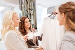 Mujeres jovenes felices que eligen la ropa en alameda Imagen de archivo libre de regalías