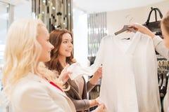 Mujeres jovenes felices que eligen la ropa en alameda Foto de archivo libre de regalías