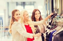 Mujeres jovenes felices que eligen la ropa en alameda Fotos de archivo