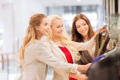 Mujeres jovenes felices que eligen la ropa en alameda Fotos de archivo libres de regalías