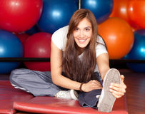 Mujeres jovenes felices que estiran en la gimnasia Imagen de archivo